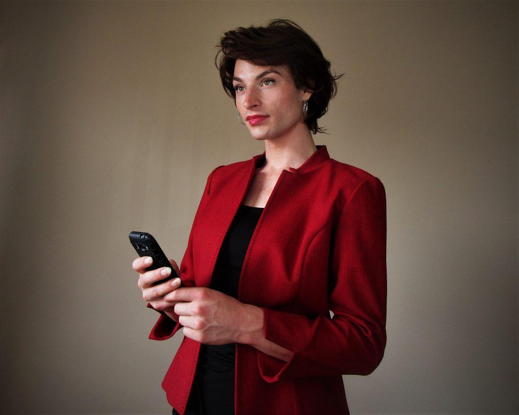 Femme traditionnelle portant une camisole noire et un veston rouge foncé.