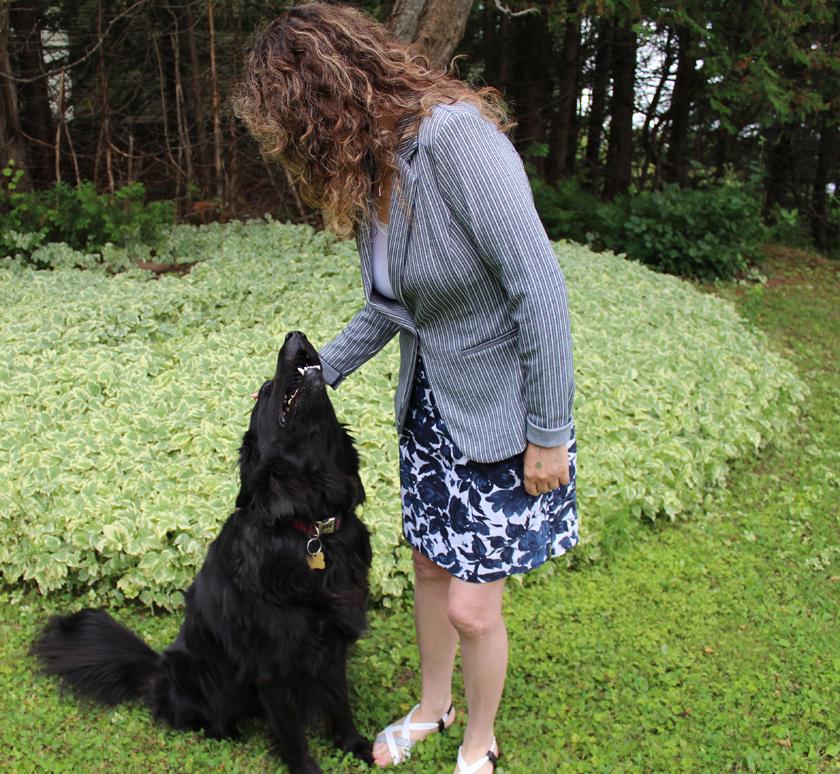 Femme debout penchée vers un  chien noir. Elle porte un veston ICHI rayé marine et blanc avec une jupe blanche avec un gors imprimé de fleurs marine.