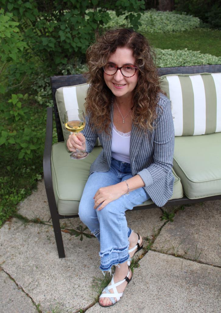 Femme aux cheveux longs bouclés assise sur une causeuse extérieure avec un verre de vin blanc à la main. Elle porte des lunettes rouges, un veston rayé marine et blanc, une camisole blanche bordée de dentelle et un jean 7/8.