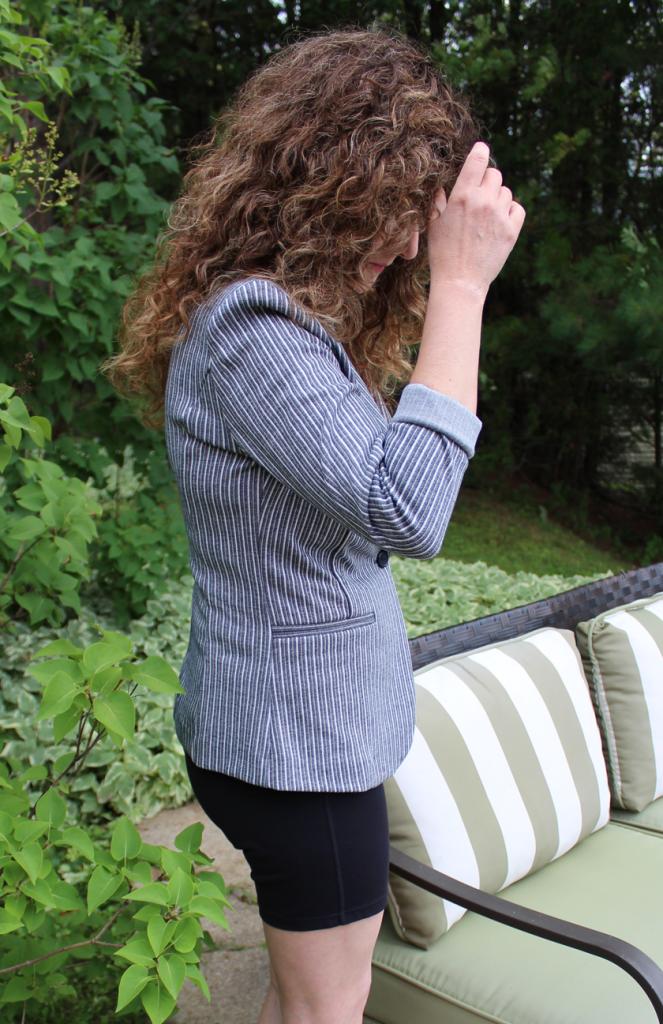 Femme portant un veston ICHI rayé marine et blanc, manches roulées aux 3/4 avec un short cycliste noir