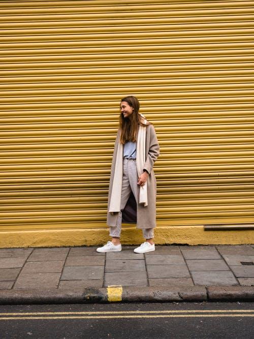 Style naturel. Femme aux cheveux longs portant un long manteau et une longue écharpe beiges sur un pantalon de coton beige et une chemise bleu pâle.
